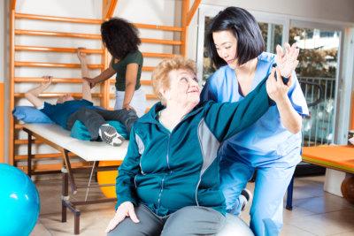 Elderly people making exercises in rehab gym
