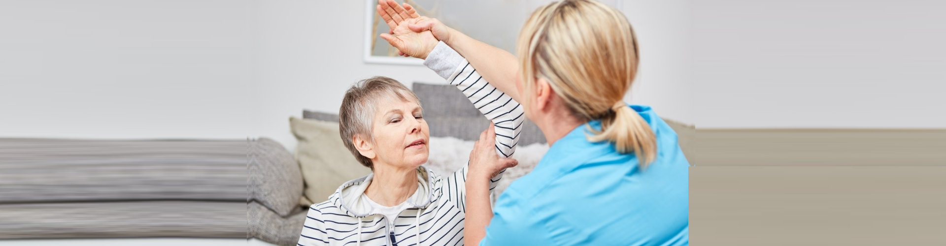 physical therapist assisting senior woman on his therapy