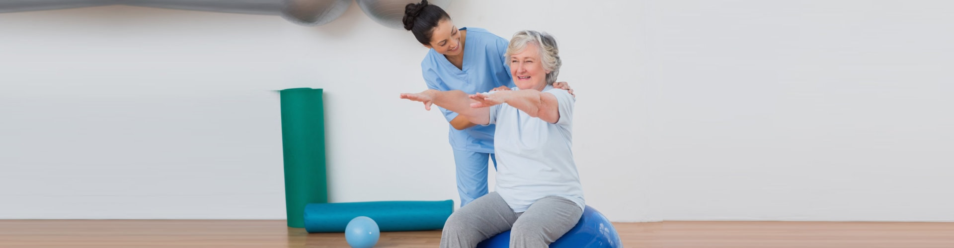 therapist assisting a senior woman sitting on an exercise ball