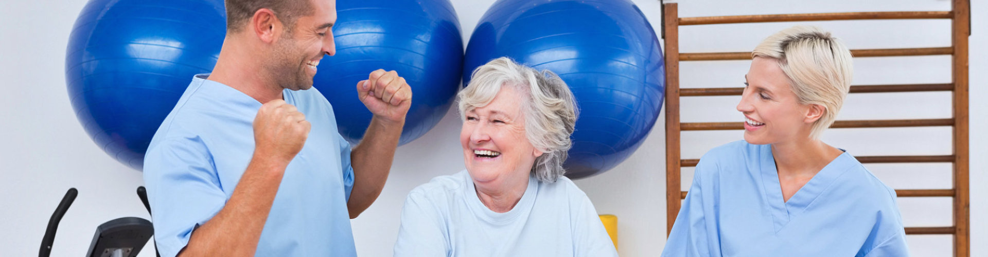 two physical therapist and senior woman smiling
